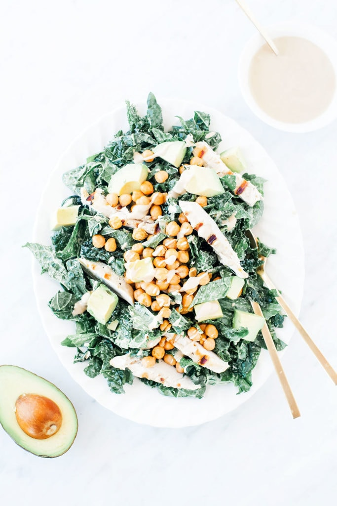 Kale tahini Caesar salad with chicken and crispy chickpeas on a white platter.
