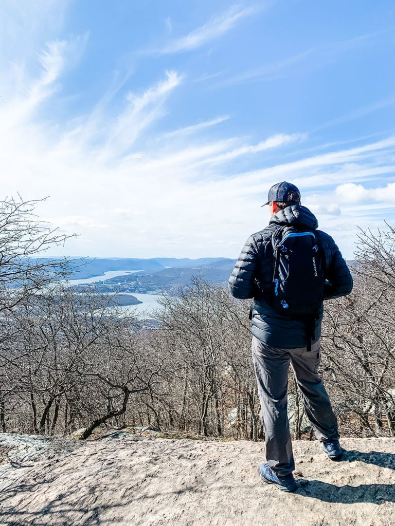Man standing on rock ledge looking onto the Hudson River.