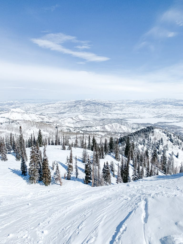 Mountains and blue sky view from the top of a snowy mountain in Park City, Utah.