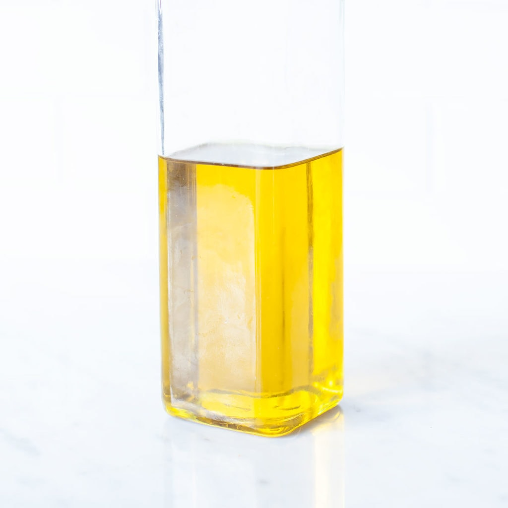 Olive oil in a clear glass bottle.