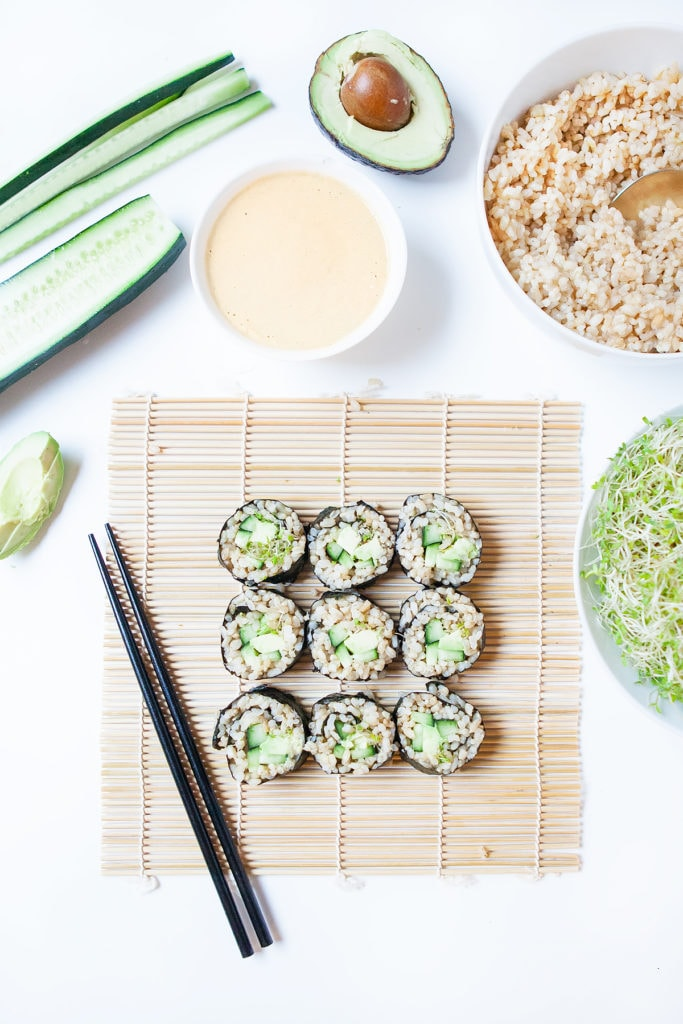 Avocado cucumber vegan sushi rolls on a bamboo sheet with a bowl of tahini miso sauce, sprouts, cucumber, brown rice, and avocado.