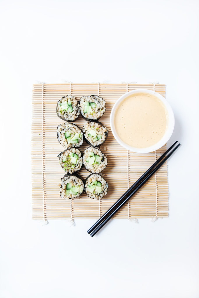 Avocado cucumber vegan sushi rolls on a bamboo sheet with a bowl of tahini miso sauce.