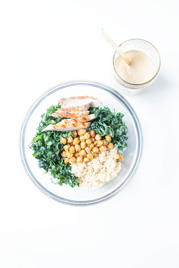 Kale tahini Caesar salad with chicken and crispy chickpeas in a glass bowl with a side of tahini sauce in a jar.