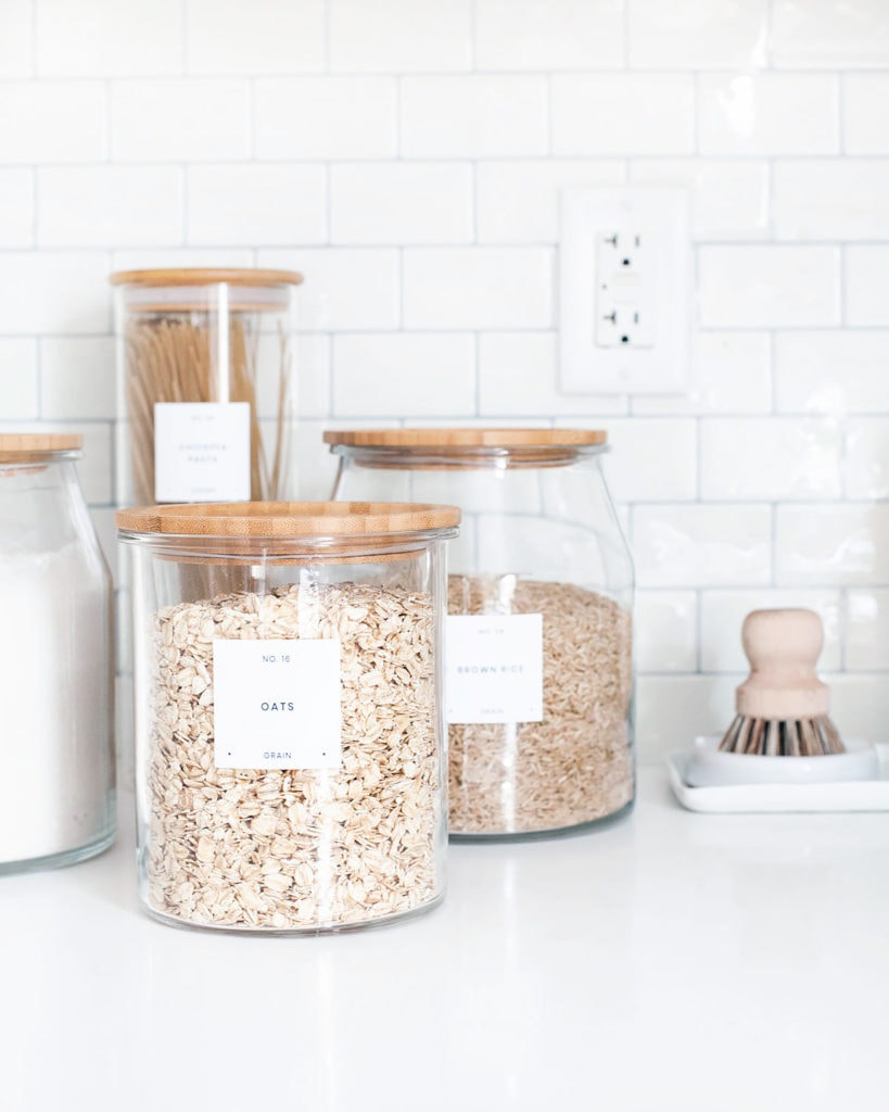 Pantry jars filled with ingredients like oats and rice on a kitchen counter with subway tile background.