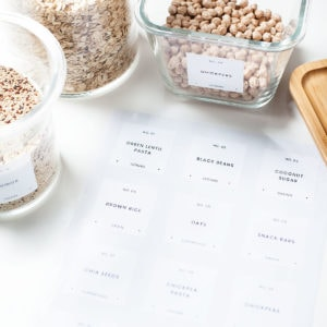 Printed modern, minimalist pantry labels and glass jars filled with pantry ingredients.