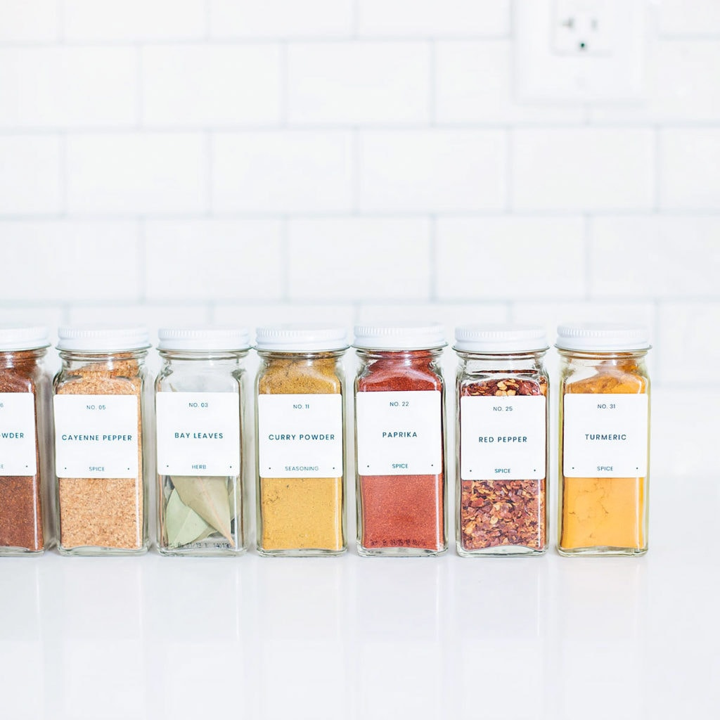 Modern, minimalist spice labels on jars with a white subway tile background.