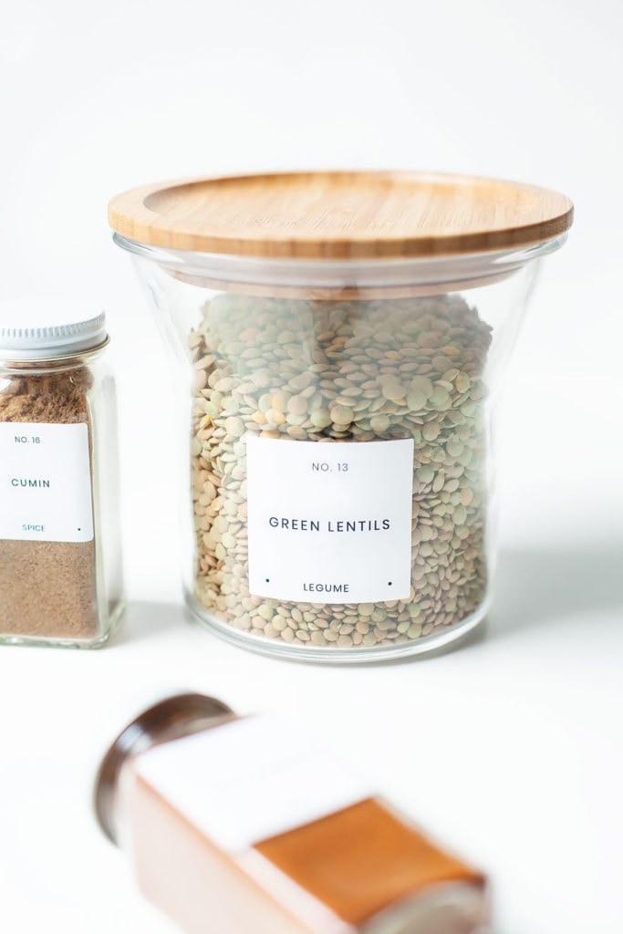 Green lentils in a jar with jars of cumin and chili powder.