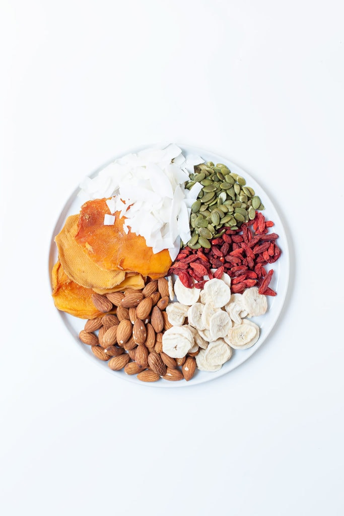 Colorful toppings, like almonds, dried bananas, goji berries, pumpkin seeds, and dried mango on a white plate.