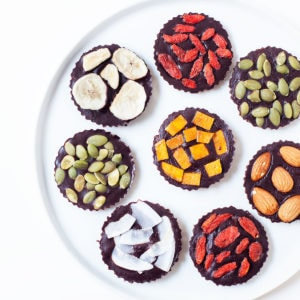 Homemade vegan chocolate with colorful toppings on a white plate.