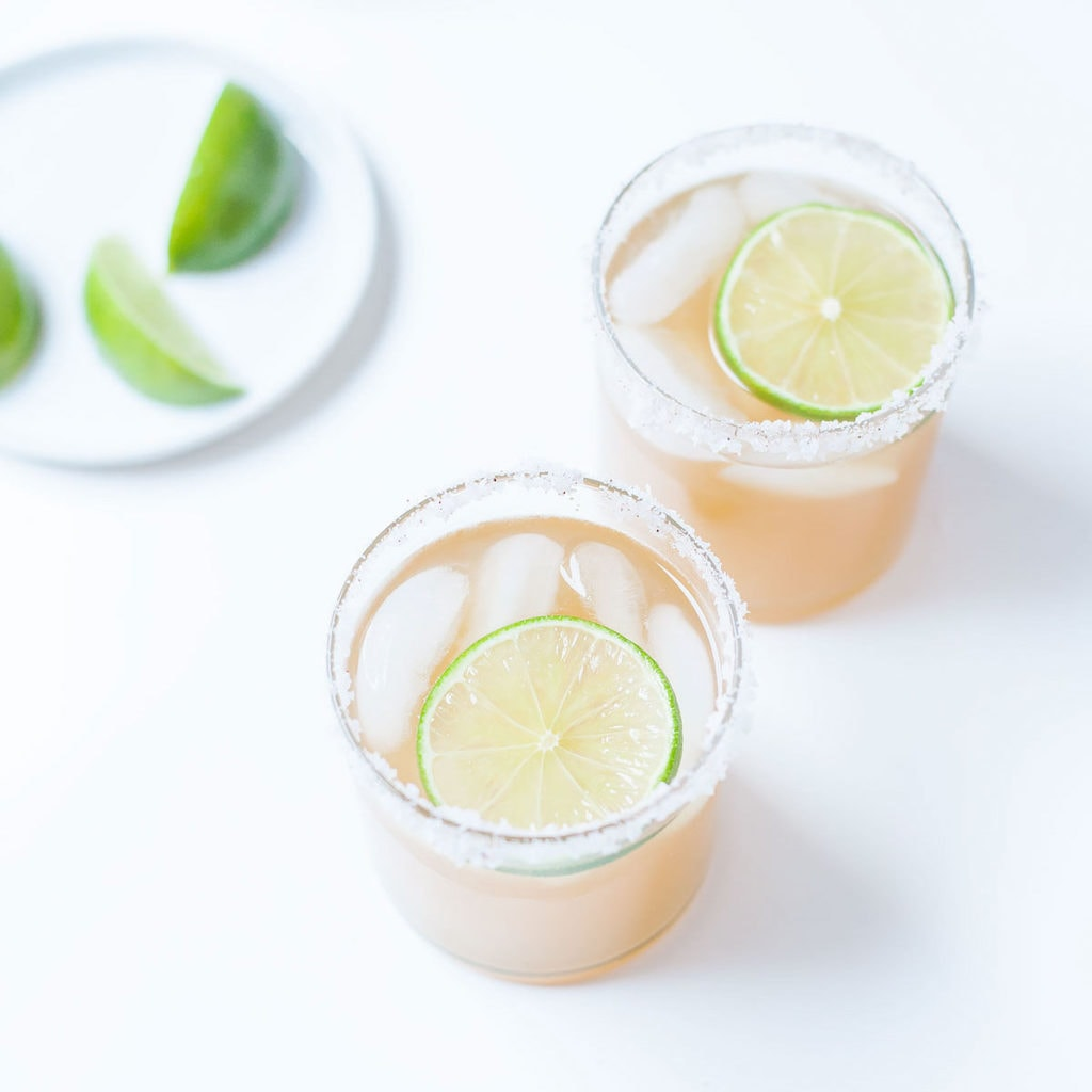 Kombucha margaritas in two cocktail glasses with lime slices.