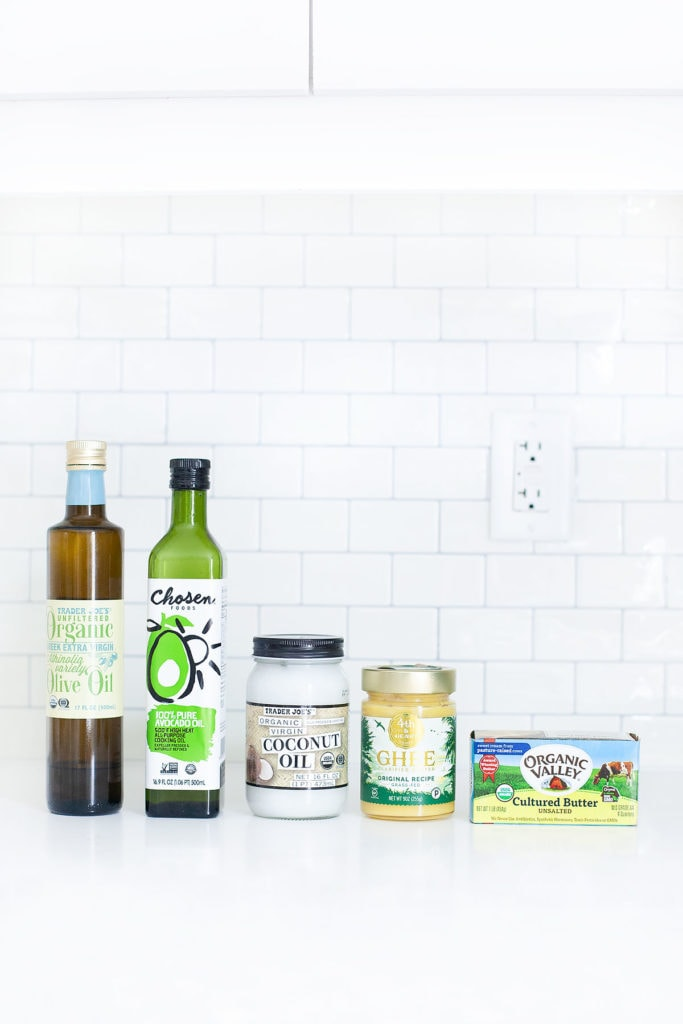 Cooking fats and oils lined up on a white countertop.