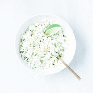 Coconut cauliflower rice with cilantro and a slice of lime in a white bowl.
