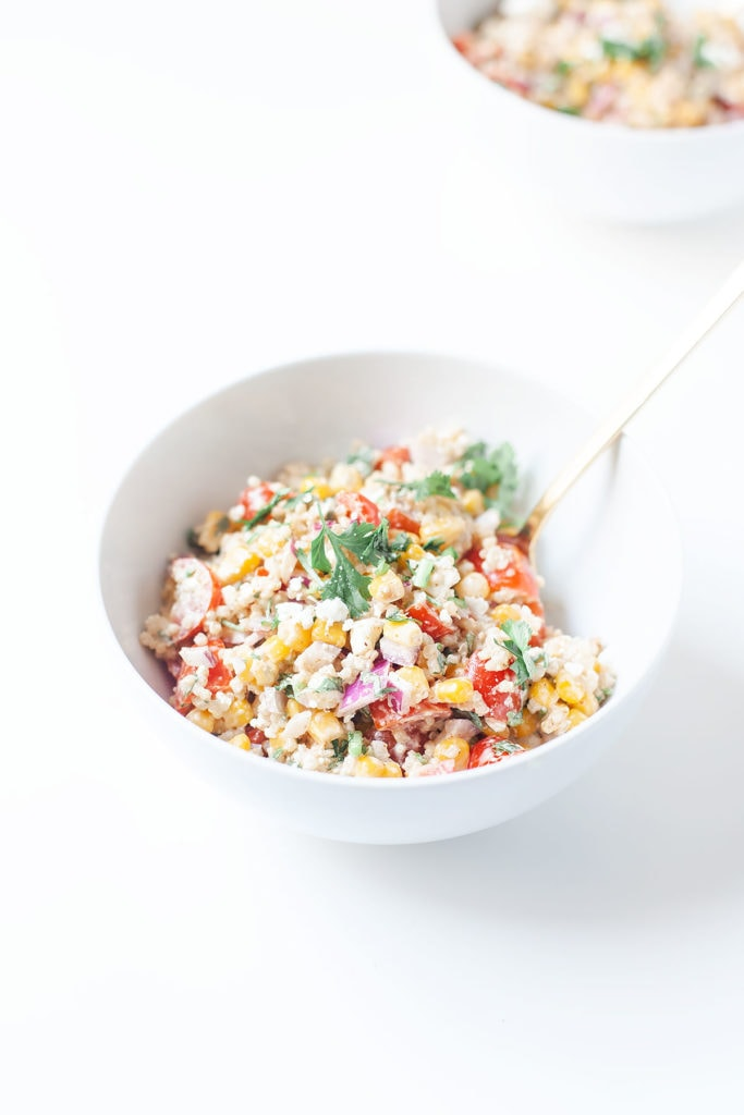 Healthy street corn salad in white bowls on a white surface.