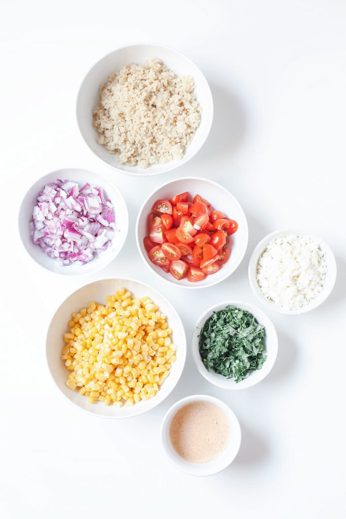 Healthy street corn salad ingredients in small white bowls on a white surface.