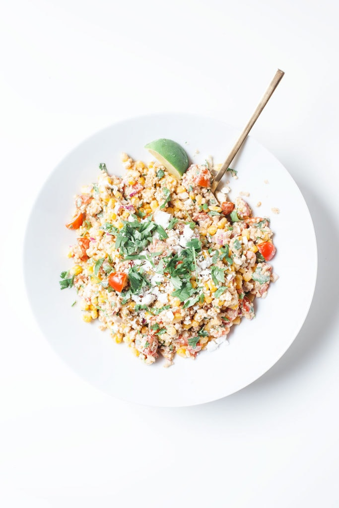 Healthy street corn salad in a white bowl on a white surface.