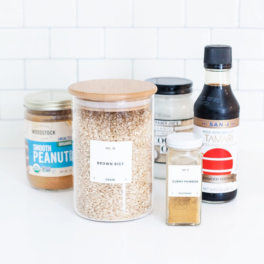 Peanut edamame burger ingredients in jars on a white countertop.