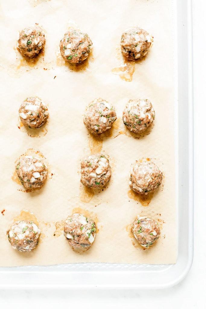 Zucchini meatballs on a baking sheet.