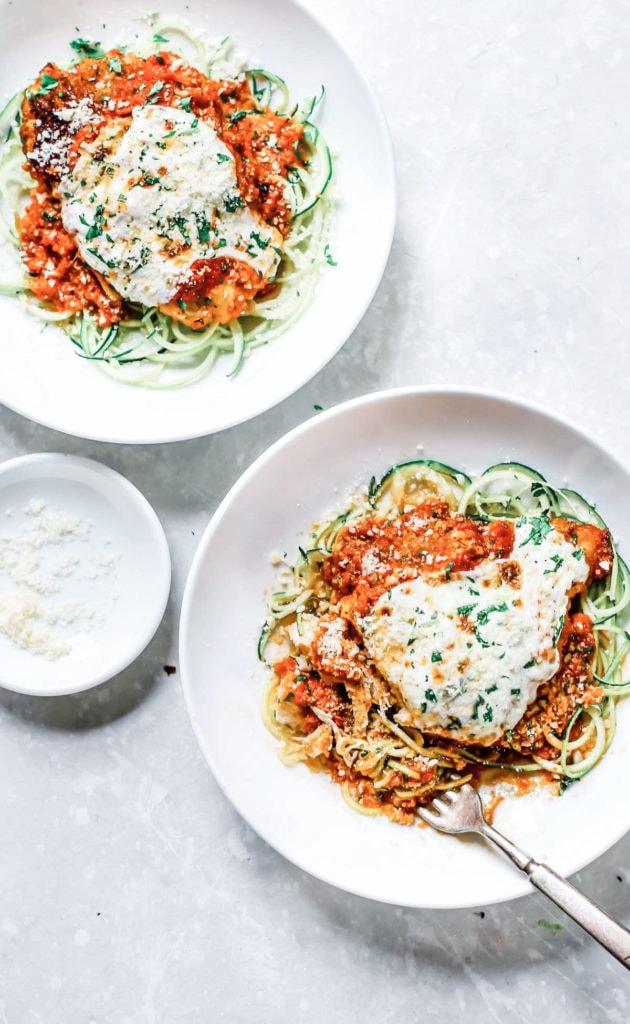 Zucchini chicken parmesan on white plates.