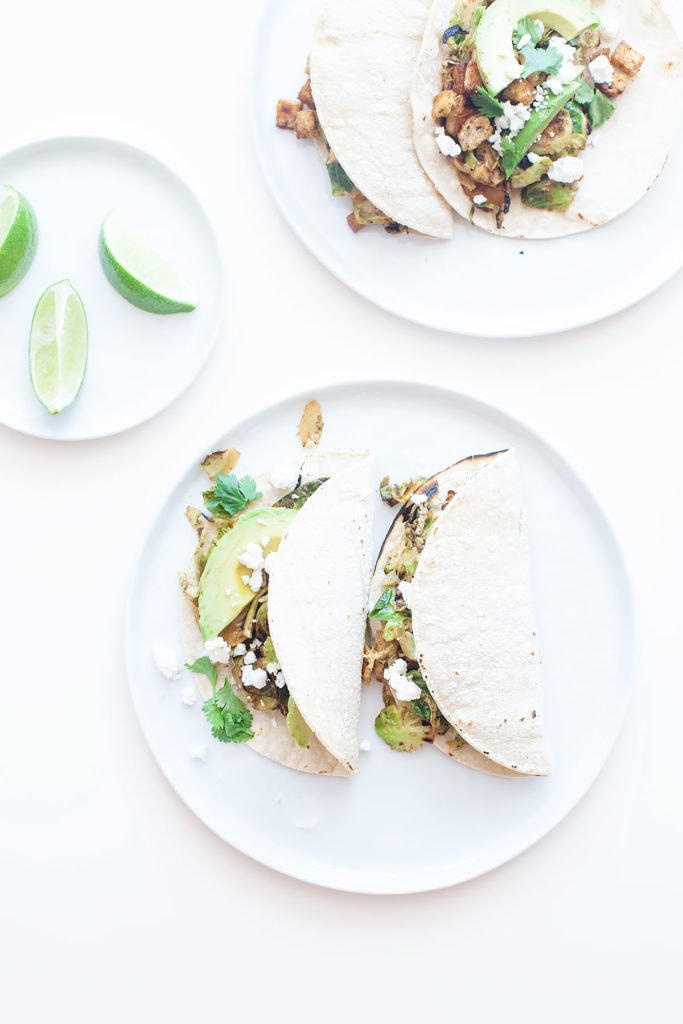Brussels sprouts tacos on a white plate with avocado and lime.