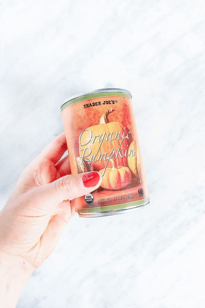 Woman's hands holding a can of pumpkin purée,
