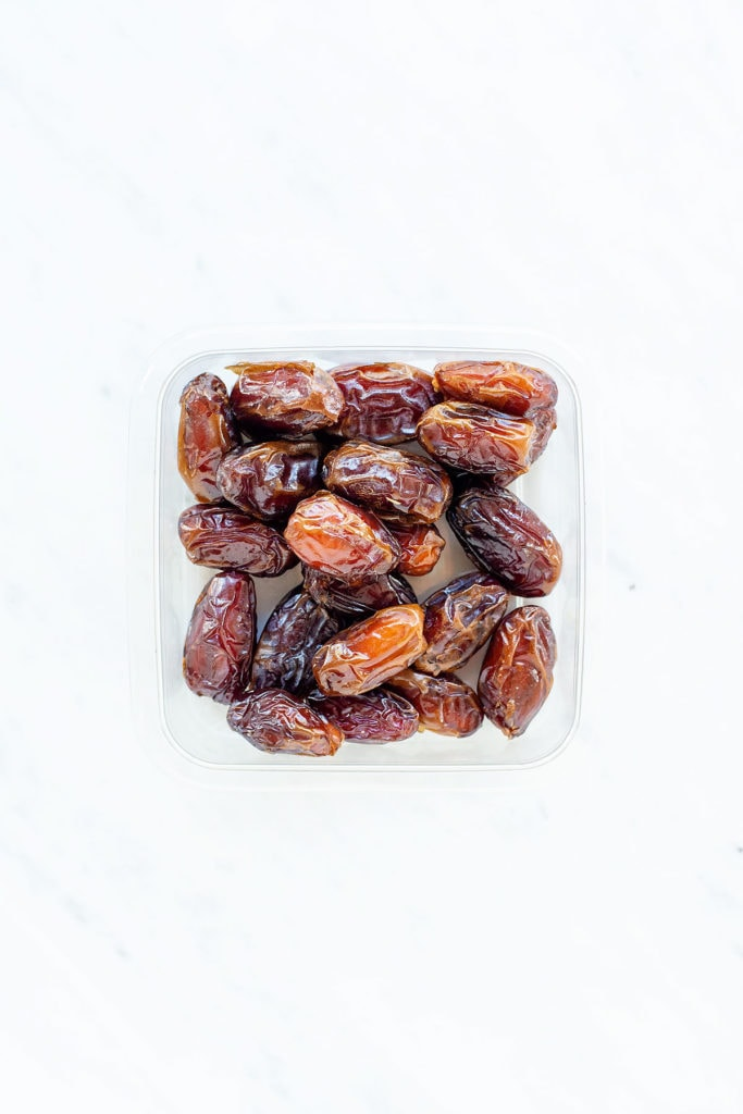 Medjool dates in a plastic container on a white counter.
