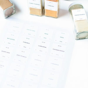 Printed spice labels being put on spice jars.