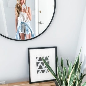 Woman smiling into a round entryway mirror.