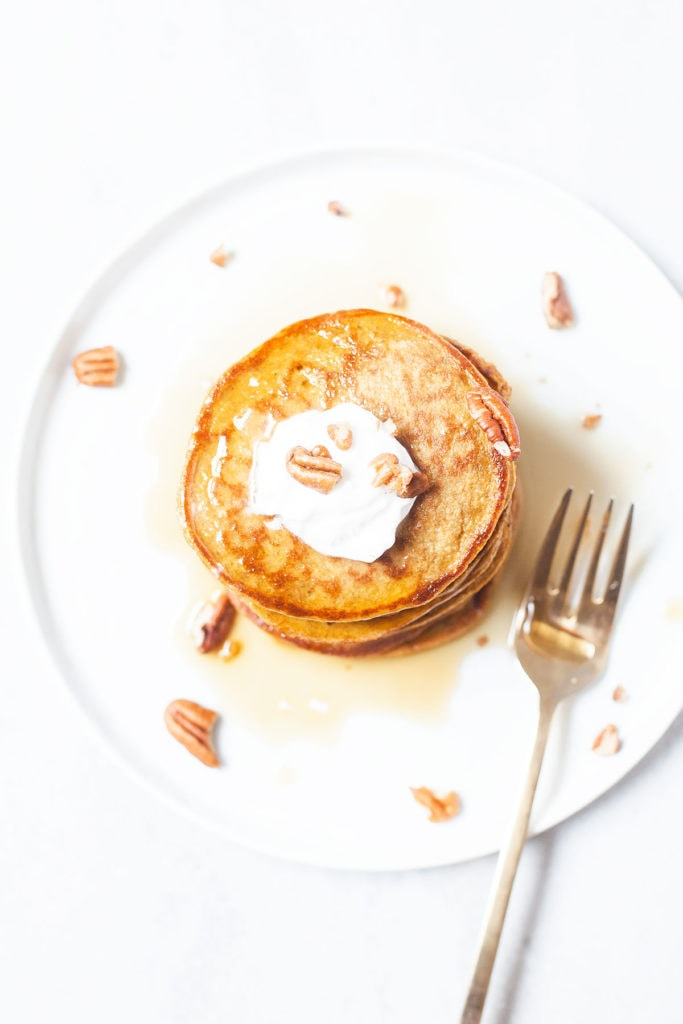 Stack of gluten-free blender pumpkin pancakes on a white plate with maple syrup and pecans.