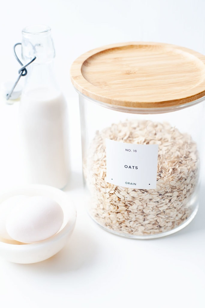 Jar of oats with eggs and non-dairy milk on a white counter top.