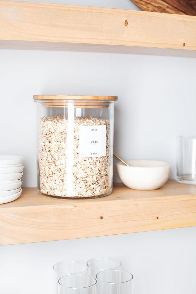 Jar of oats on wooden open shelves.