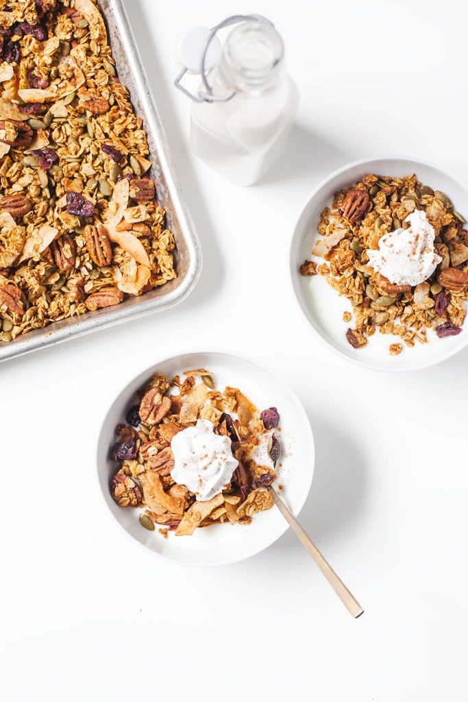 Low-sugar pumpkin granola in two bowls with dollops of coconut whipped cream.