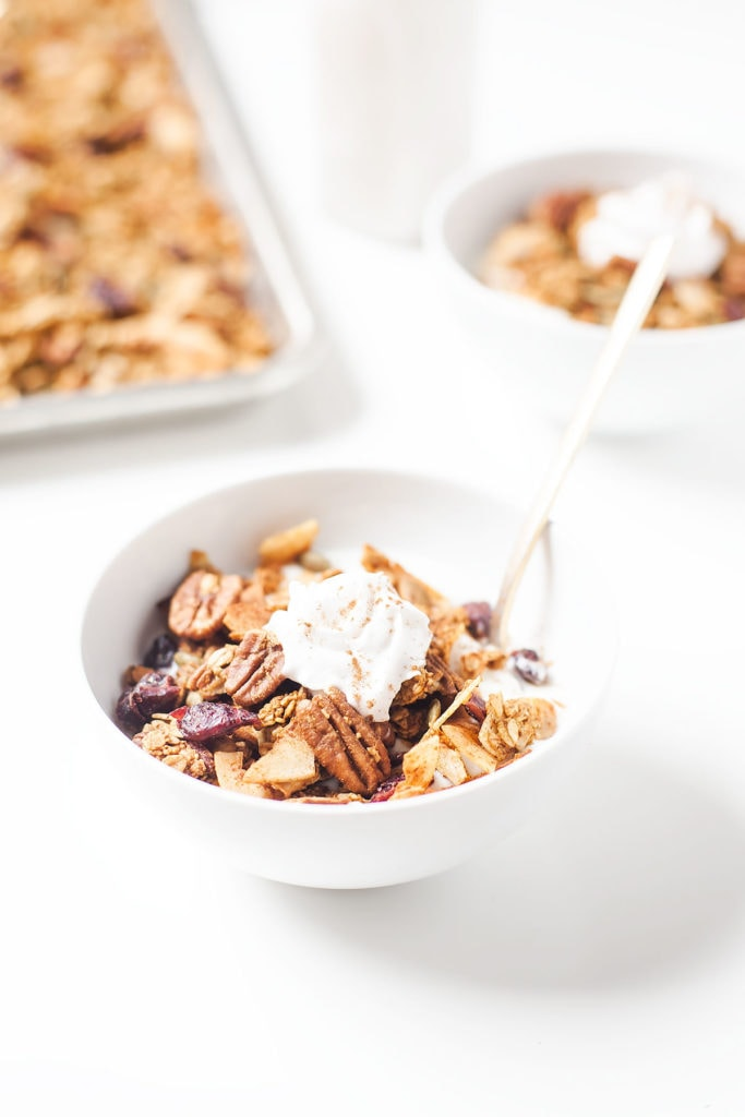 Low-sugar pumpkin granola in a white bowl with a dollop of coconut whipped cream.