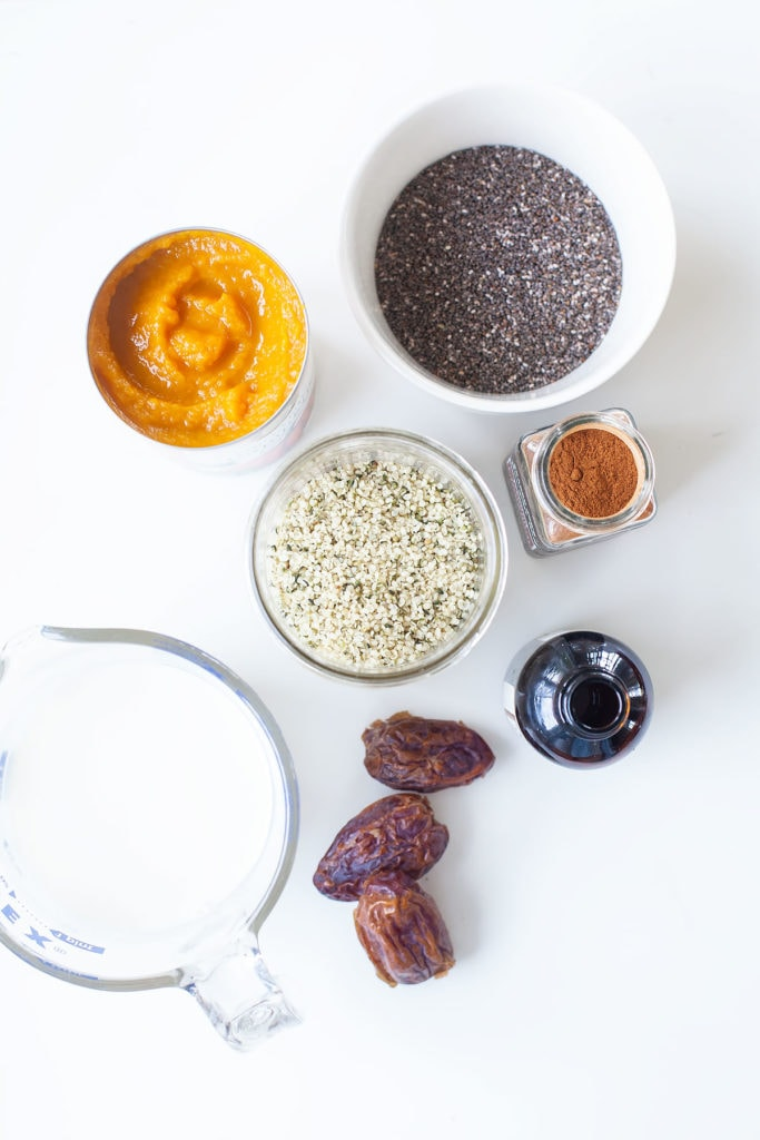 Pumpkin chia hemp seed pudding ingredients on a white table.