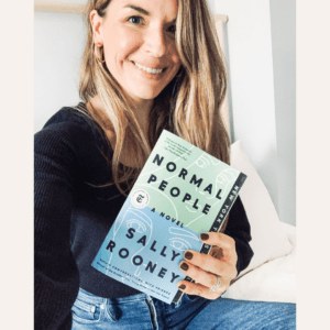 Woman sitting on a bed smiling and holding a copy of the book Normal People.