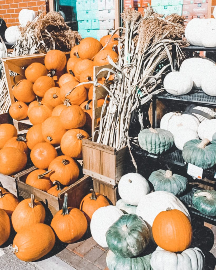 Pumpkins outside of a grocery store.