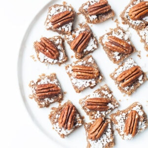 Pecan pie bars on a white plate.