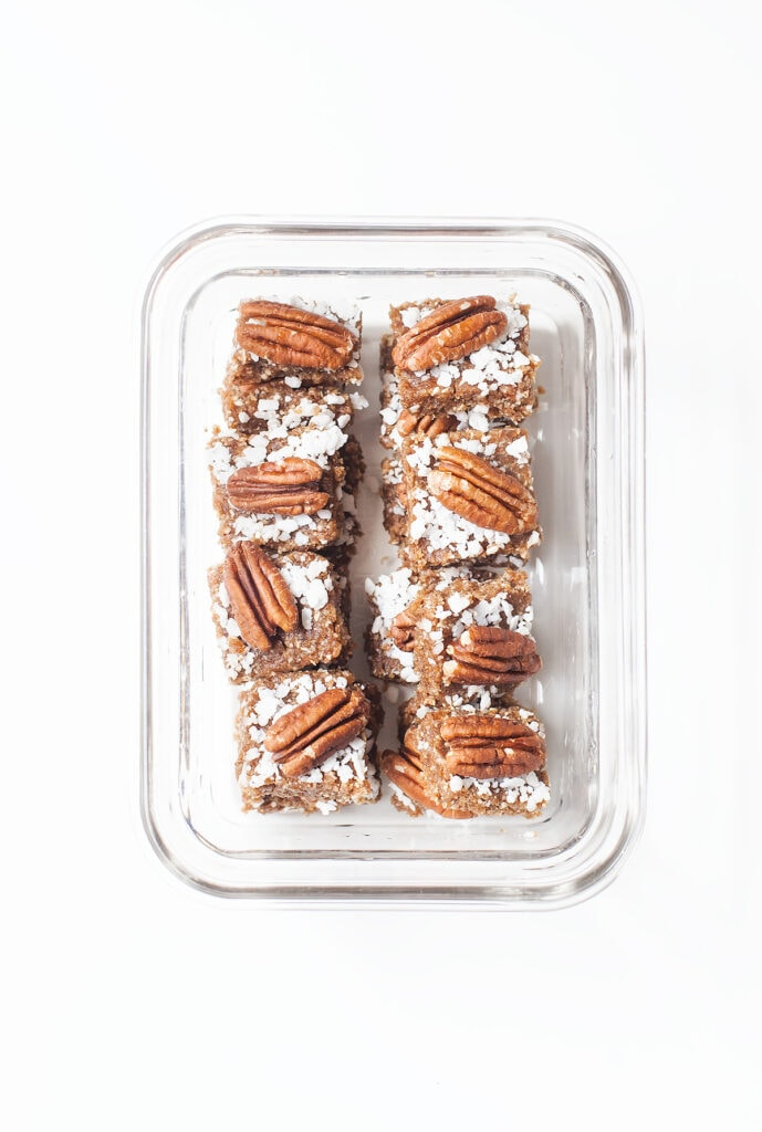 Pecan pie bars in a glass container.
