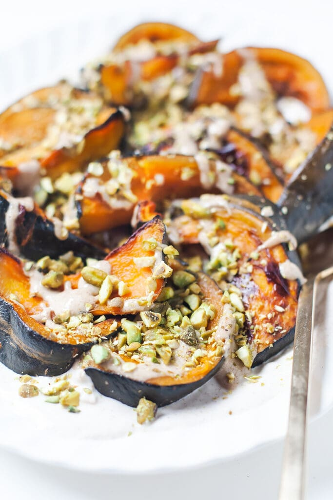 Kabocha squash with tahini yogurt and pistachios on a white platter.
