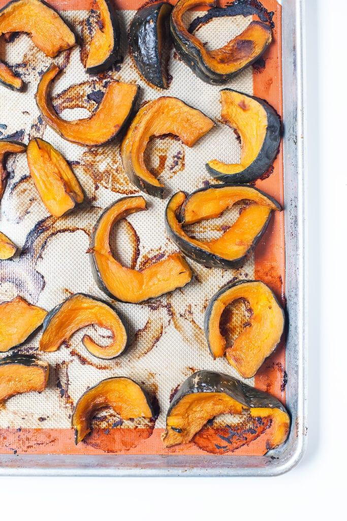 Kabocha squash slices on a baking sheet.