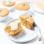 Gluten-free rosemary cornbread muffins on a white surface with a pat of butter.
