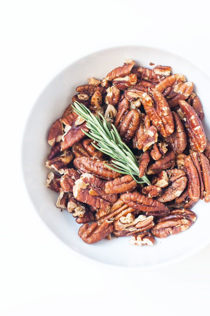 Rosemary maple pecans in a white bowl.