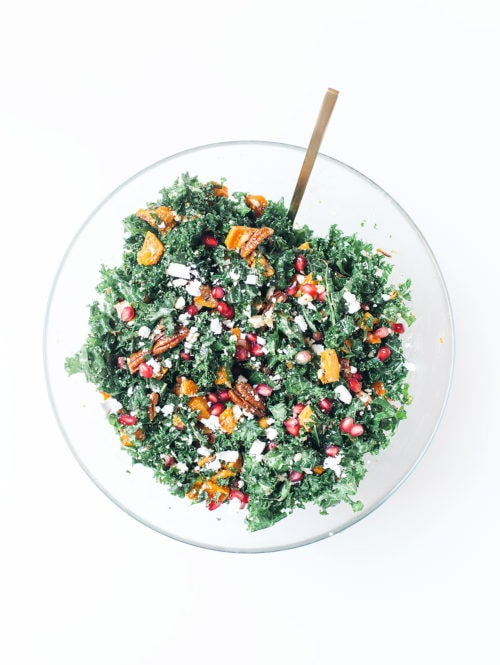 Thanksgiving kale salad with pomegranates, pecans, and butternut squash in a large glass bowl.