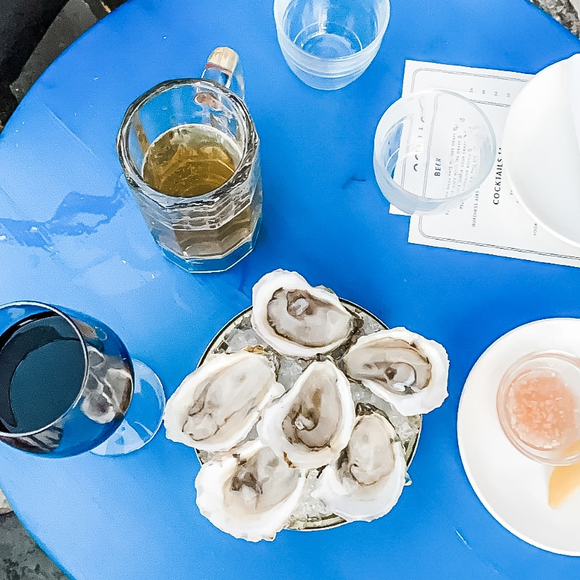 Blue tabletop with oysters, wine, and beer.