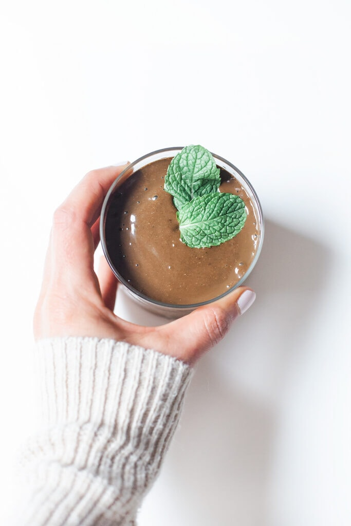 Simple mint chocolate smoothie in a glass with mint leaves and hand holding the glass.
