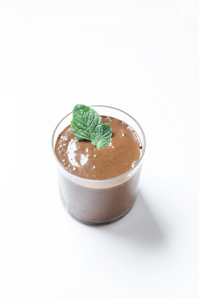 Simple mint chocolate smoothie in a glass with mint leaves.