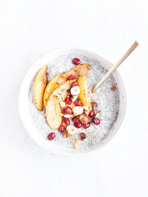 Cinnamon pear chia pudding in a white bowl with a spoon.