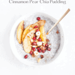 Cinnamon pear chia pudding in a white bowl with a spoon being held by a hand.