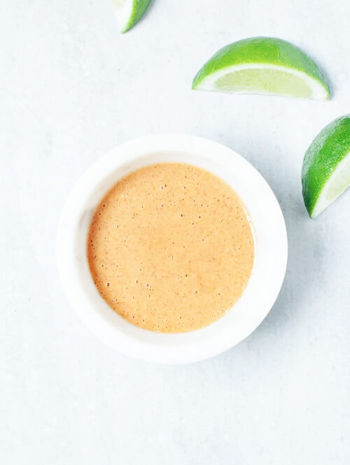 Coconut peanut sauce in a white bowl with lime slices on the side.