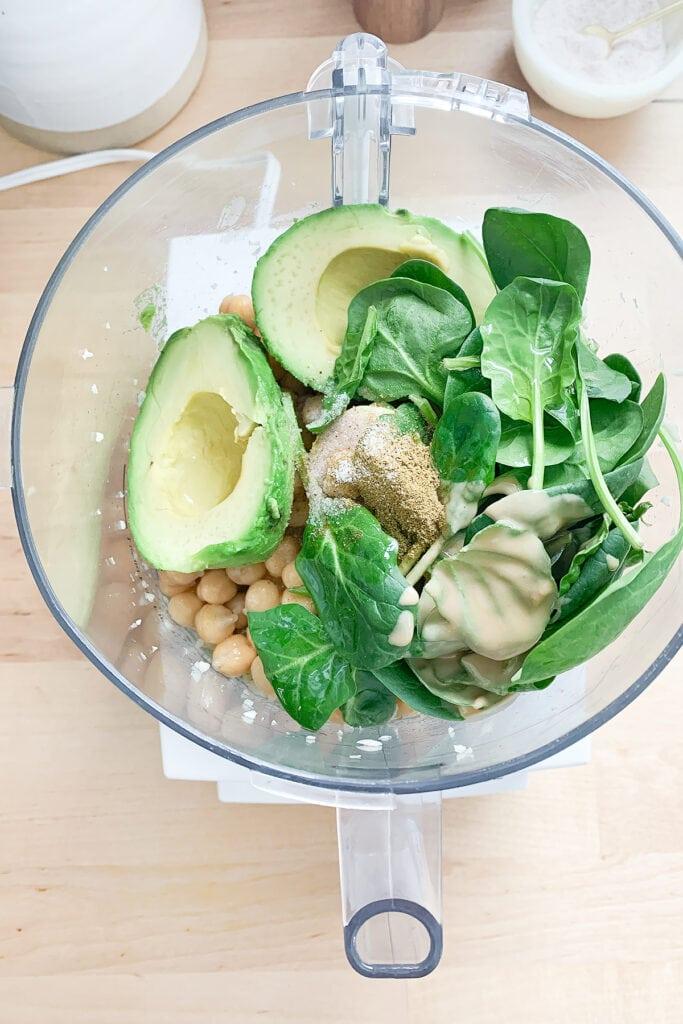 Avocado hummus ingredients in a food processor.