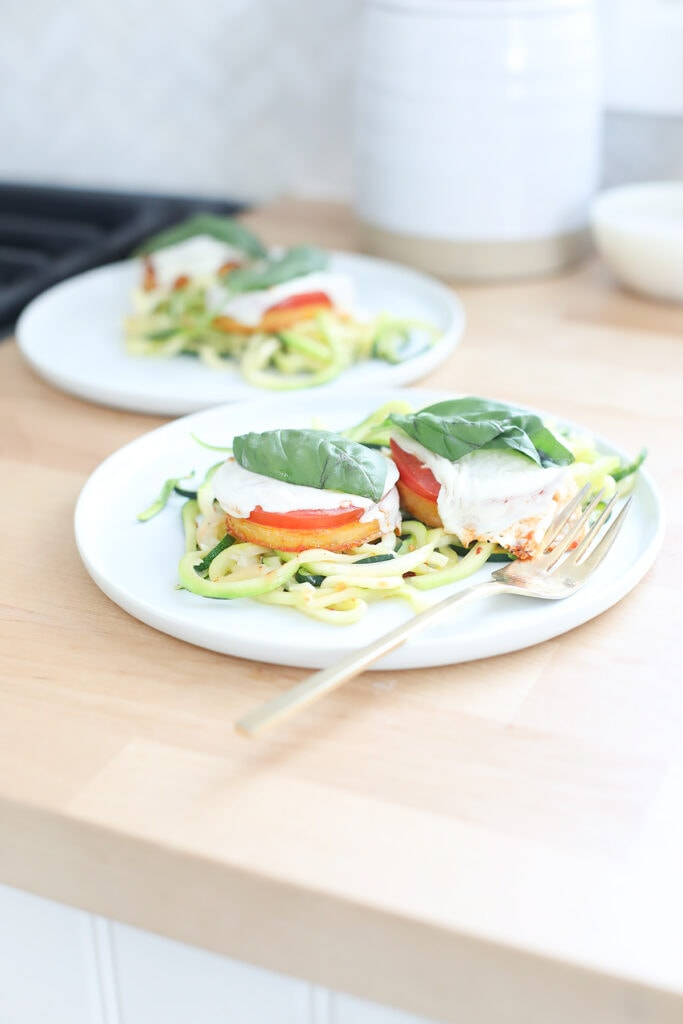Baked polenta margherita pizzas with zucchini noodles on white plates.